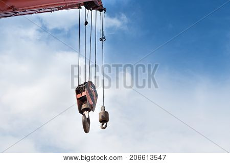 Crane hook weight lifting up to 50 tons against blue sky background.
