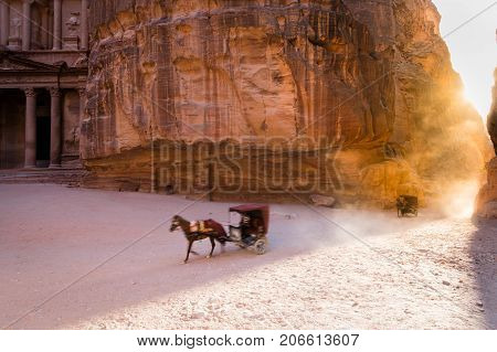 A touristic horse carriage retreats back through the Siq (corridor) and passes in front of Petra's most famous touristic site the Treasury in Petra Jordan.