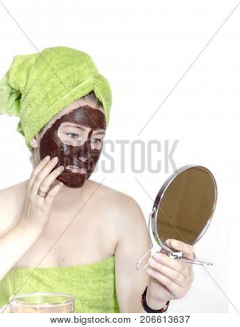 Girl with chocolate cosmetic mask on her face looks in the mirror