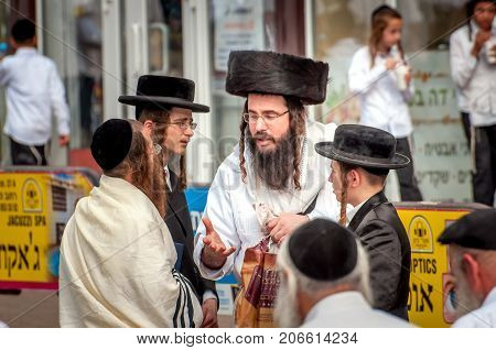 A group of Hasidim pilgrims in traditional clothing emotionally talk. Uman Ukraine - September 21 2017: Rosh hashanah holiday Jewish New Year.