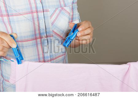 Woman Hands Hanging Wet Clean Cloth To Dry On Clothes Line At Laundry Room on a grey background
