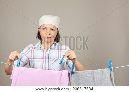 Attractive Woman Hanging Wet Clean Cloth To Dry On Clothes Line At Laundry Room on a grey background