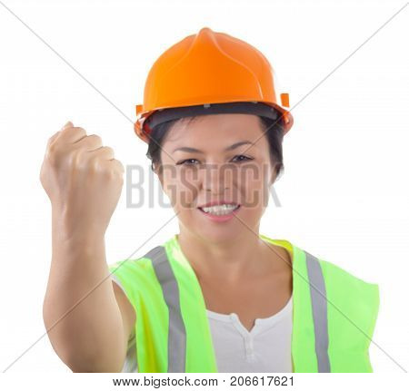Wicked Attractive Woman Worker in Safety Jacket and Yellow Helmet Making a Threat with a Fist on a white background