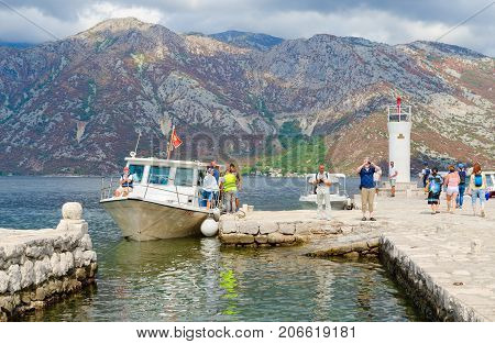PERAST MONTENEGRO - SEPTEMBER 10 2017: Unknown tourists visit Island of Virgin on reef (Gospa od Skrpela Island) Montenegro