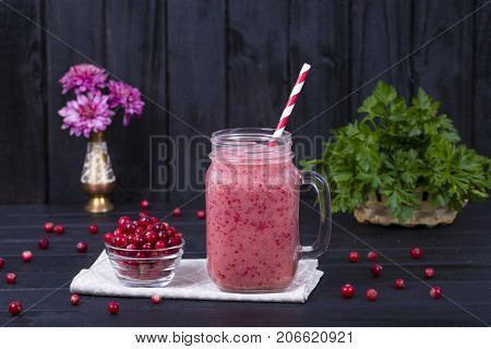 Cranberry Juice Smoothie Shake In Glass Mug And Raw Cranberry On Black Wooden Background, Close Up