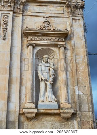 Ostuni, Italy - August 12, 2017. Saint Francis statue in facade of Chiesa di San Francesco church in Piazza della Liberta square of Ostuni La Citta Bianca (The White Town) Apulia Italy.