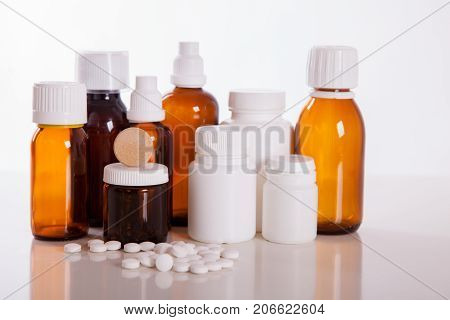 health care traditional medicine and flu concept - tea cup with lemon and pills. Medical pills and hot tea with lemon treatment of colds flu and runny.