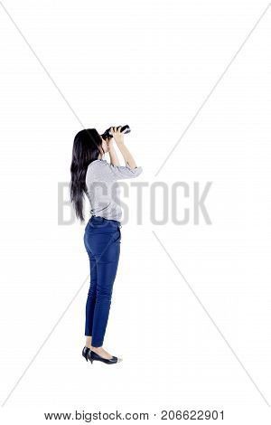 Side view of young businesswoman looking through a binocular while standing in the studio