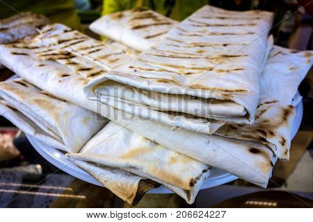 Fresh Armenian lavash is stacked on a plate. Thin armenian bread.
