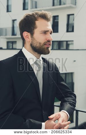 Relaxed Businessman Standing On Balcony Of His Apartment