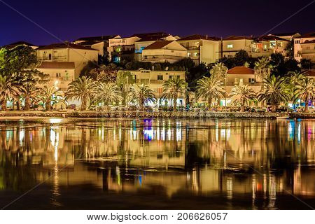 Night waterfront view at small town in suburb of town Split, Stobrec townscape, Croatia.