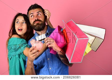 Couple Holds Shopping Bags And Hug On Pink Background.