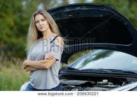 traveller girl near a car with a raised hood