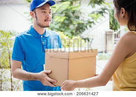 woman accepting receive a delivery of boxes from delivery asian man sign and receive delivery concept (focus on box)