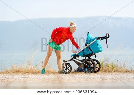 Mother with child in stroller enjoying motherhood at sunset and mountains landscape. Jogging or power walking woman with pram at sunset. Beautiful inspirational mountains landscape.