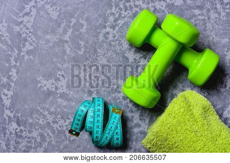 Tape Measure And Towel Near Plastic Barbells