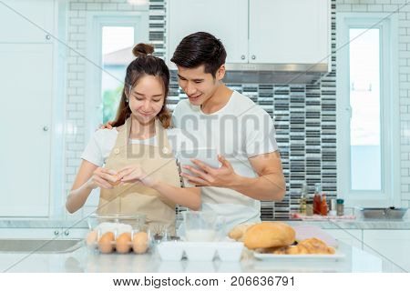 Young couple together cooking Woman first crack an egg and put in a bowl Man holding tablet looking menu for dinner bakery bread cake with milk in kitchen room at home.