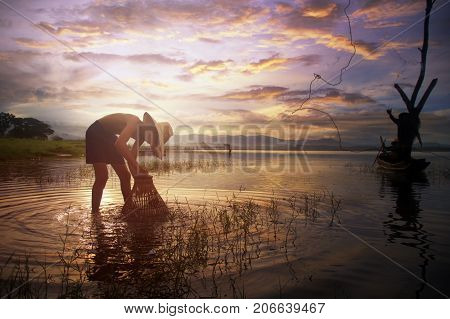 Asian young fisherman casting freshwater fish in nature river in the early morning before sunrise.