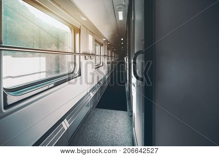 Wide-angle shooting of long and empty double-decker passenger train interior with multiple closed doors of compartments hills outside the windows carpet on the floor railings on the walls