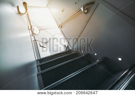Wide-angle view from bottom of modern staircase with floor illumination going up to second floor of two-storey contemporary passenger train; railing on both sides dustbin and mirror in a distance