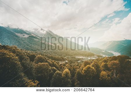 Stunning wide-angle scenery from high point of beautiful autumn mountains ridges overgrown with forests low clouds misty valley with resort settlement Estosadok Sochi district Russia