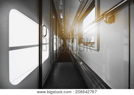 Wide-angle shooting of bright long and empty two-storied passenger train interior with multiple closed doors of compartments sunny day outside the windows carpet on the floor railings on the walls