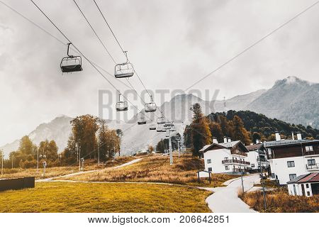 Autumn landscape: ropeway stretching into distance over hills with houses of Olympic village trees cell connection towers meadows and the road; low clouds Estosadok district Sochi Russia