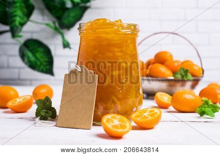 Jam from kumquat with rind in glass on a wooden background. Selective focus.