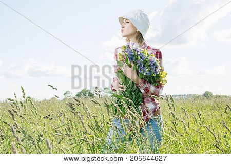 A girl in the field collects flowers field flowers in a basket a young girl with a smile dressed in a shirt in a red box in denim shirts and in a cappella he goes and breaks colored (blue and yellow) flowers in a green field (meadow).