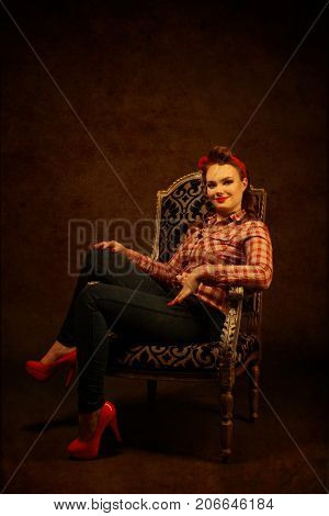 Young pretty pinup girl red button shirt siting in chair dark background retro vintage 50's style. Human emotions body language