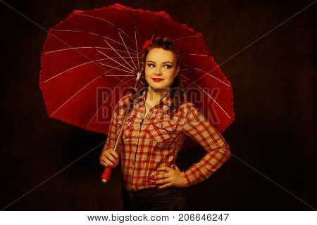Young pretty pinup girl red button shirt looking aside dark color background retro vintage 50's style with red umbrella.