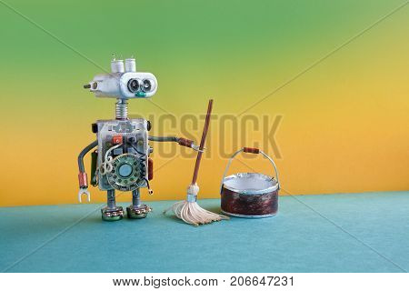 Cleaning room service concept. Robotic washer with mop and bucket of water, mopping floor. Creative design toy cyborg funny head, electronic parts body. Green yellow background.