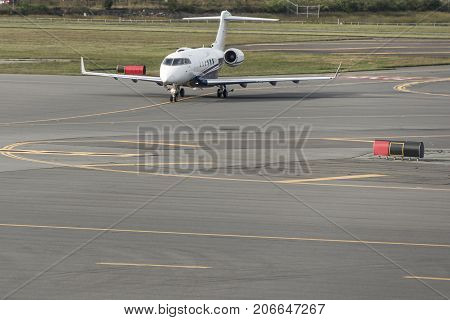 business jet airplane or aircraft with open door on airfield near of airport terminal
