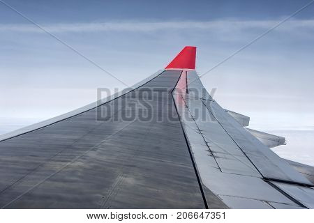 wing airplane in the sky red winglet blue sky clouds