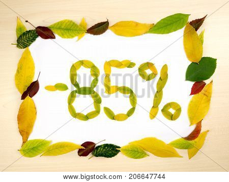 Word 85 percent made of autumn leaves inside of frame of autumn leaves on wood background. Eighty five percent sale. Autumn sale template