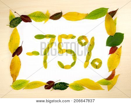 Word 75 percent made of autumn leaves inside of frame of autumn leaves on wood background. Seventy five percent sale. Autumn sale template