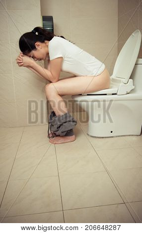 Attractive Pretty Woman Sitting On Bathroom Toilet