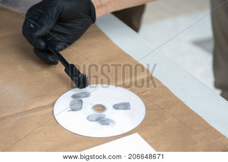 forensic hand in glove brushing latent fingerprints evidence by white powder on compact disc with copy space