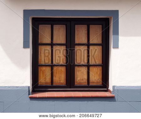 traditional old wooden window with glass panes closed internal shutters on a clean white house wall with gray painted surround and lower area in bright sunlight