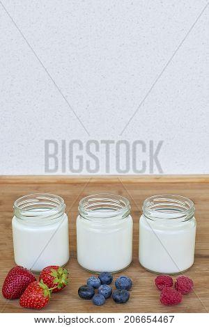 Three glass jars with yogurt and variation of berries - vertical