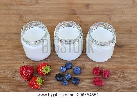 Three glass jars with yogurt and variation of berries - close up
