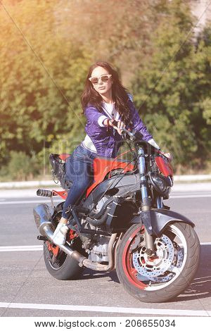 Fashionable young woman with sunglasses lilac short windbreaker and jeans with a beautiful body on a red sports bike.