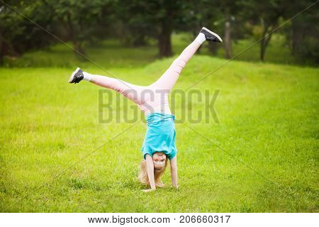 Cute athletic schooler girl tumbling turning turn handsprings in the park. Sunny summer day. Sport for children. Kid doing gymnastic and having fun. Healty body.