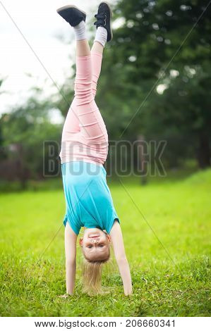 Cute athletic schooler girl tumbling turning turn handsprings in the park having fun. Sunny summer day. Sport for children. Kid doing gymnastic and having fun. Healty body.