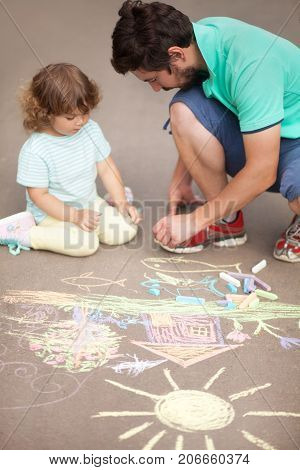 Caring father happy family. Drawing with color chalk. Sunny summer days. Happy childhood. Preschooler leisure time. Kids spending time with parents. Artistic talented kids. Colorful chalk drawing. Children's drawings. Father and daughter relationships.