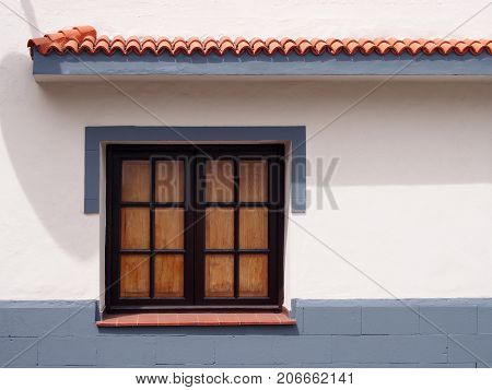 traditional old wooden window with glass panes closed internal shutters on a clean white house wall with gray painted surround and lower area with clay tiled veranda in bright sunlight