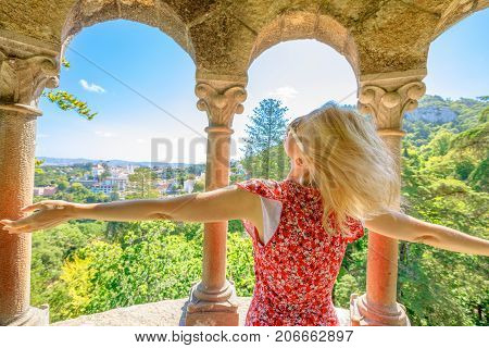 Carefree blonde caucasian woman with open arms looking Sintra panorama. Female tourist enjoying in a sunny day. Aerial view of Sintra National Palace on blur background.Travel and tourism in Portugal.