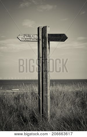 Old wooden sign on the beach in Spurn Point near Hull UK
