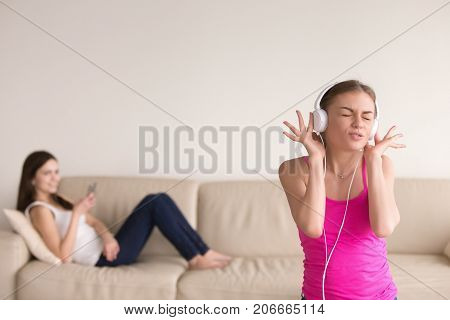 Young girl in stylish white headphones listening to favorite music and singing, making funny face. Her girlfriend relaxing on sofa with smartphone in hand, laughing at her friend for being silly.