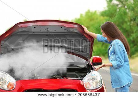 Young woman standing near broken car